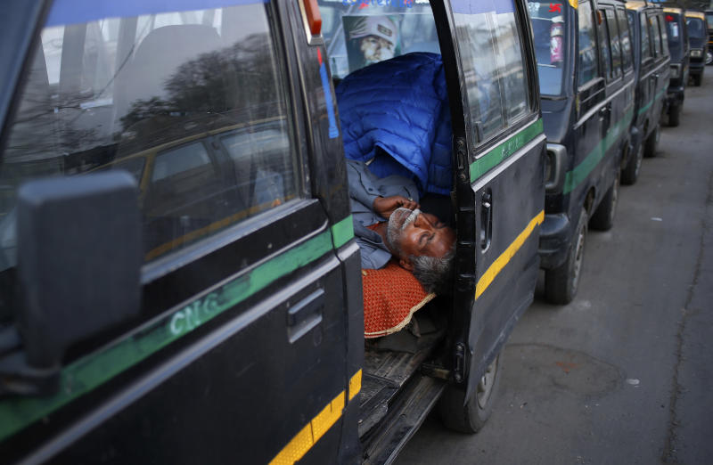 In this Monday, March 24, 2014 photo, an Indian taxi driver sleeps inside his traditional black-and-yellow licensed cab as he waits for customers in New Delhi, India. Most licensed taxis are banned from having air conditioning under an archaic municipal rule, leaving passengers suffering with rolled-down windows in suffocating heat and noxious pollution. Taxi-hailing smartphone app Uber is making a big push into Asia with the company starting operations in 18 cities in Asia and the South Pacific including Seoul, Shanghai, Bangkok, Hong Kong and five Indian cities in the last year. (AP Photo/Saurabh Das)