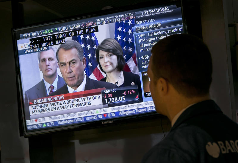 Specialist Frank Masiello watches a television monitor on the floor of the New York Stock Exchange showing a Washington news conference by House Speaker John Boehner, Tuesday, Oct. 15, 2013. Leaders in the House of Representatives and Senate were negotiating separate but similar plans Tuesday to reopen the U.S. government and prevent a default on American debt that economists say could tip the global economy back into recession. (AP Photo/Richard Drew)
