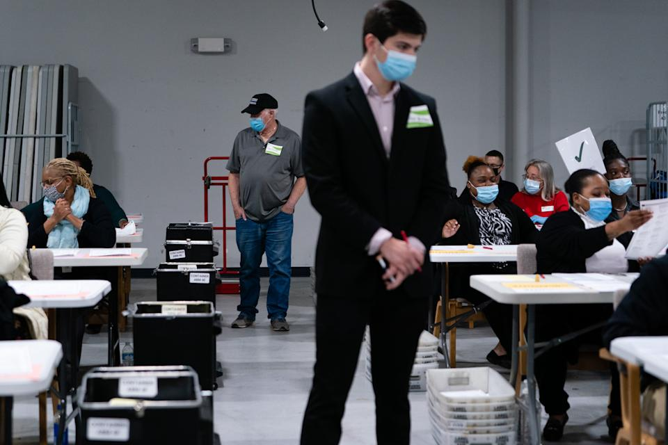 Political party representatives monitor people hand counting 2020 Presidential election ballots during an audit at the Gwinnett County Voter Registration office. (Photographer: Elijah Nouvelage/Bloomberg via Getty Images)