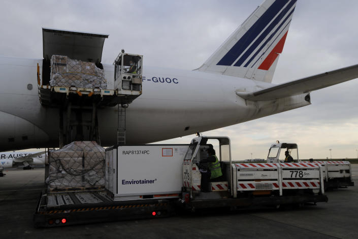FILE - In this Wednesday, Nov. 25, 2020 file photo, Air France cargo workers load equipment and pharmaceutical containers onto a cargo plane at Roissy airport, outside Paris, as the company is preparing for the transport of COVID-19 vaccines. A last-minute trade deal with the United Kingdom coupled with the rollout of COVID-19 vaccines in the final days of the year produced a sense of success for the 27-nation bloc and brought glimmers of hope to the EU's 450 million residents. (AP Photo/Christophe Ena, File)