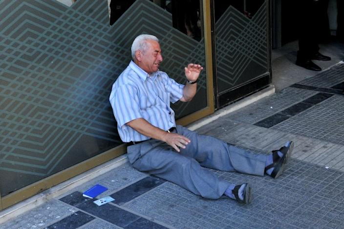 Greek pensioner, Giorgos Chatzifotiadis, cries as he sits on the ground outside a national bank branch in Thessaloniki on July 3, 2015 (AFP Photo/Sakis Mitrolidis)