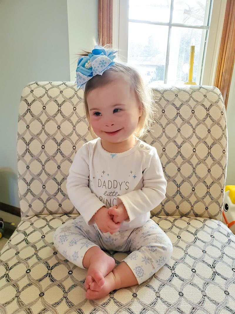 Ivy, a toddler girl with Down syndrome sitting on a chair, wearing a big blue bow in her hair.