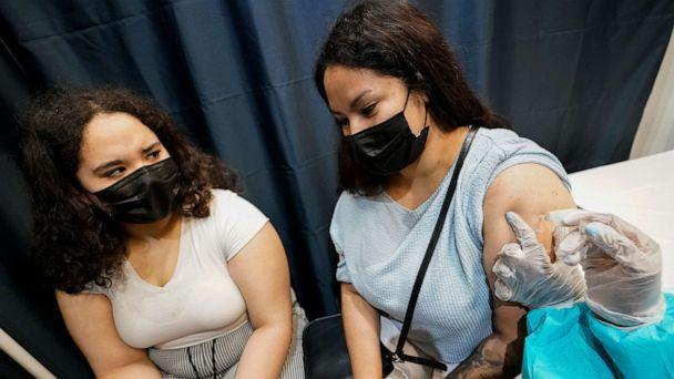 PHOTO: A health care worker inoculates Evelyn Pereira, right, of Brooklyn, with the first dose of the Pfizer COVID-19 vaccine as her daughter Soile Reyes, 12, looks on, July 22, 2021, at the American Museum of Natural History in New York. (Mary Altaffer/AP)