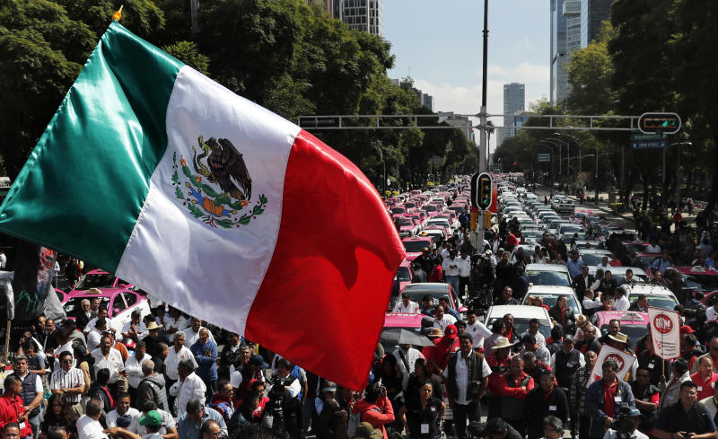 A Mexican national flag is waved as hundreds of taxi drivers gather to protest ride apps, in Mexico City, Monday, Oct. 7, 2019. The protesters want the apps banned, arguing that the apps are unfair competition because those drivers are more loosely regulated and don't have to pay licensing fees. (AP Photo/Marco Ugarte)