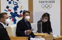 Sebastian Coe, center, the president of World Athletics, an internationally governing organization for the sport of athletics, watches the media leave the room as he starts to talk with Tokyo Gov. Yuriko Koike in Tokyo on Friday, May 7, 2021. Seiko Hashimoto, the president of the Tokyo Olympic organizing committee, said Friday IOC President Thomas Bach to make a planned visit this month to Japan with a state of emergency order being extended by the government until May 31 to Tokyo and other areas. (AP Photo/Hiro Komae)
