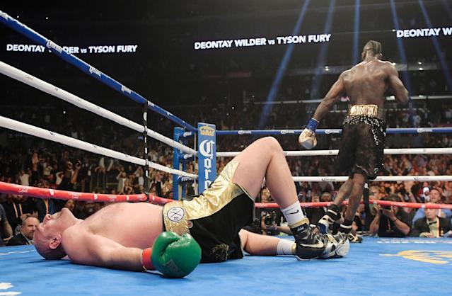 Tyson Fury lies on the canvas after being knocked down by Deontay Wilder during the 12th round of a WBC heavyweight championship boxing match in Los Angeles. The bout ended in a split draw. (AP Photo)