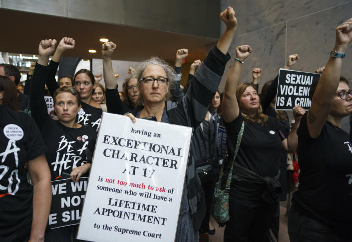 Protesters opposed to Supreme Court nominee Brett Kavanaugh stand quietly with fists raised in the Hart Senate Office Building on Capitol Hill in Washington, D.C., on Sept. 24, 2018. (Photo: Carolyn Kaster/AP)