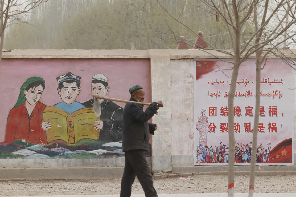 """A farmer walks past government propaganda depicting ethnic minority residents reading the constitution with slogans which reads, """"Unity Stability is fortune, Separatism and Turmoil is misfortune,"""" near Kashgar in northwestern China's Xinjiang Uyghur Autonomous Region on March 19, 2021. Four years after Beijing's brutal crackdown on largely Muslim minorities native to Xinjiang, Chinese authorities are dialing back the region's high-tech police state and stepping up tourism. But even as a sense of normality returns, fear remains, hidden but pervasive. (AP Photo/Ng Han Guan)"""
