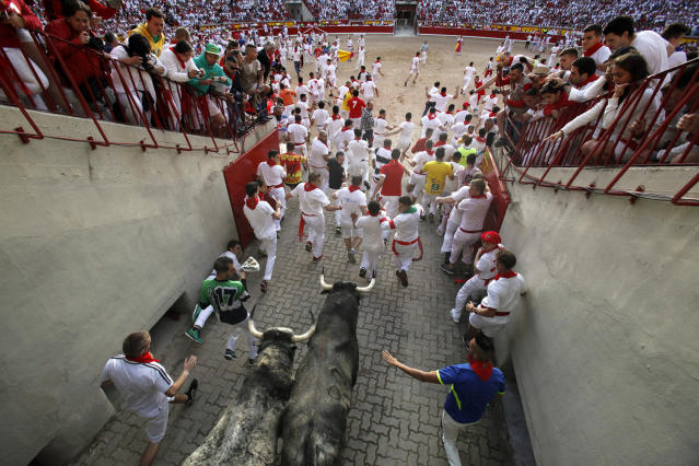 <p>Revellers run with Cebada Gago's fighting bulls entering the bullring during the second day of the San Fermin Running of the Bulls festival on July 7, 2017 in Pamplona, Spain. (Pablo Blazquez Dominguez/Getty Images) </p>