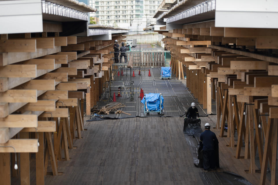 Construction workers fold a tarp sheet at a closed building complex being built as part of the athletes' village to be used during the postponed Tokyo 2020 Olympic and Paralympic Games, in Tokyo Thursday, April 8, 2021. Many preparations are still up in the air as organizers try to figure out how to hold the postponed games in the middle of a pandemic. (AP Photo/Hiro Komae)