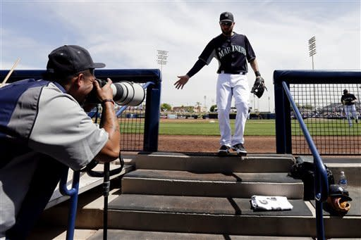 Seattle Mariners pitcher Felix Hernandez, left, uses a photographer's camera to take pictures of second baseman Dustin Ackley, center right, and others as they leave the field during the second inning in an exhibition spring training baseball game, Tuesday, March 26, 2013, in Peoria, Ariz. (AP Photo/Gregory Bull)