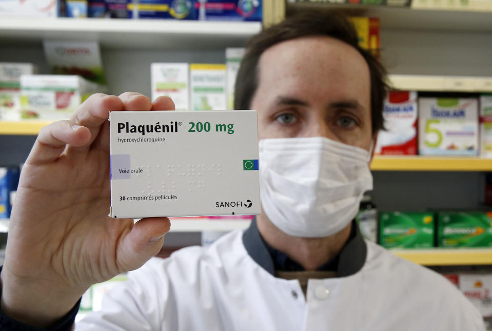 A pharmacy worker wears a protective mask shows a box of Plaquenil, also known as hydroxychloroquine, on March 25, 2020 in Paris, France. (Photo: Chesnot/Getty Images)