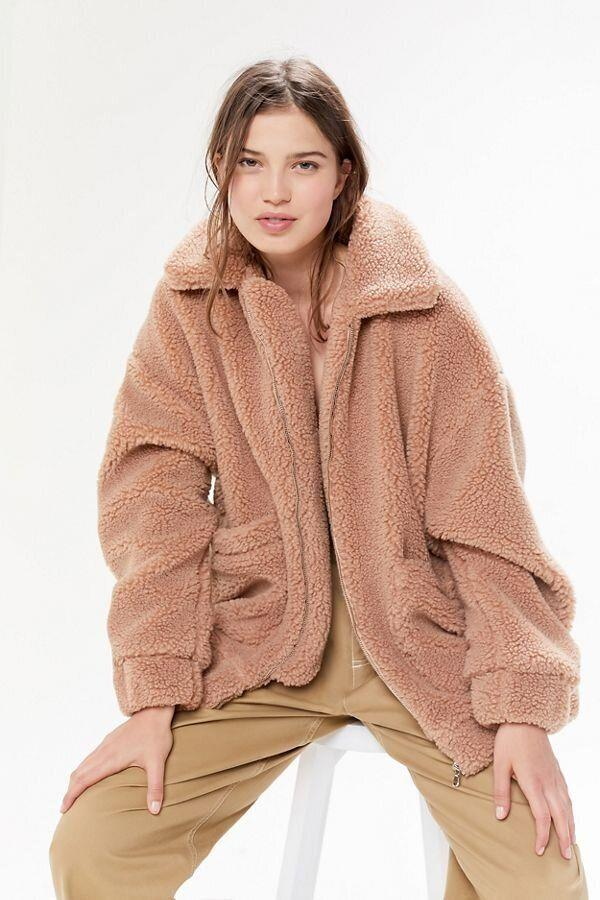 "This short tan teddy coat has a zip-front, oversized silhouette with a pointed collar abd pouch pockets, plus banding at the cuffs and hem.&nbsp;<strong><a href=""https://fave.co/2A5fCe3"" target=""_blank"" rel=""noopener noreferrer"">Find it for $120 at Urban Outfitters</a></strong>."