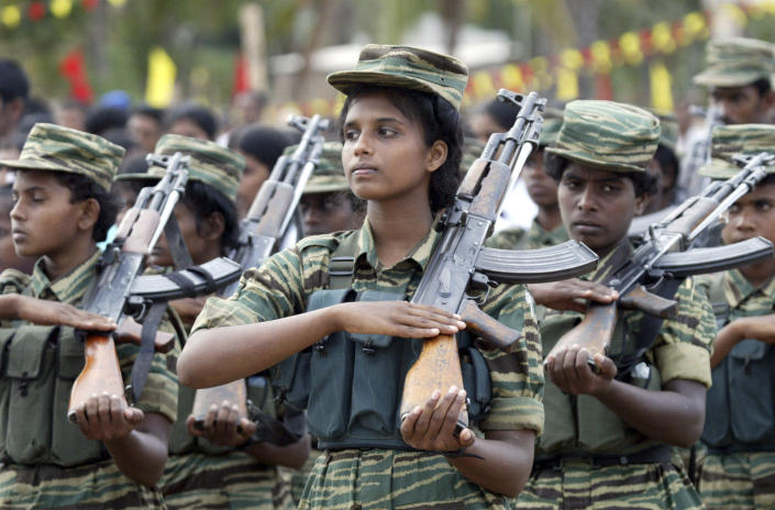 FILE - In this July 5, 2006, file photo, Sri Lankan Tamil Tiger rebels salute during an annual memorial for suicide cadres at the rebel controlled eastern town of Kovilporativu in Batticaloa, Sri Lanka. The April 21, 2019 deadly Easter attacks in Sri Lanka are a bloody echo of decades past in the South Asian island nation, when militants inspired by attacks in the Lebanese civil war helped develop the suicide bomb vest. Over nearly 30 years of civil war, the Tamil Tigers would launch more than 130 suicide bomb attacks, making them the leading militant group in such assaults at the time. (AP Photo/Eranga Jayawardena, file)