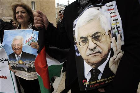 Palestinians hold posters depicting President Mahmoud Abbas during a rally in the West Bank town of Bethlehem March 17, 2014. REUTERS/Ammar Awad