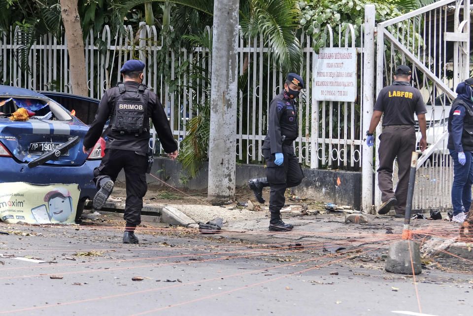 Police investigators collect evidence from around the site of a bomb attack at the Sacred Heart of Jesus Cathedral in Makassar, South Sulawesi, Indonesia, Monday, March 29, 2021. Two attackers believed to be members of a militant network that pledged allegiance to the Islamic State group blew themselves up outside the packed Roman Catholic cathedral during a Palm Sunday Mass on Indonesia's Sulawesi island, wounding a number of people, police said. (AP Photo/Masyudi S. Firmansyah)