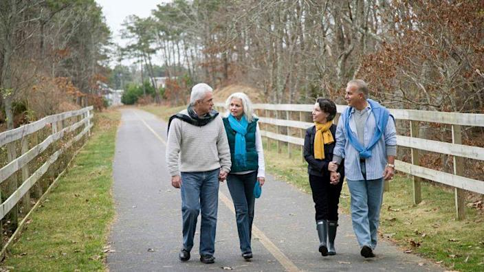Two couples walk on a path side-by-side.