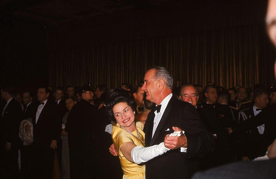 """<p>Lyndon Johnson shares the first dance at his inaugural ball with his wife, Lady Bird Johnson. The new First Lady wore a yellow satin ball gown designed by John Moore. The dress was later <a href=""""https://www.si.edu/newsdesk/photos/lady-bird-johnsons-inaugural-coat-1965"""" rel=""""nofollow noopener"""" target=""""_blank"""" data-ylk=""""slk:gifted to the Smithsonian"""" class=""""link rapid-noclick-resp"""">gifted to the Smithsonian</a> for preservation. </p>"""