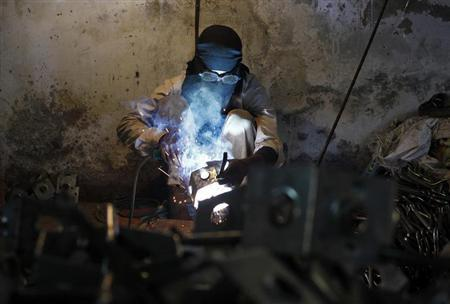An employee works inside a electrical equipments manufacturing unit in New Delhi December 2, 2013. REUTERS/Anindito Mukherjee