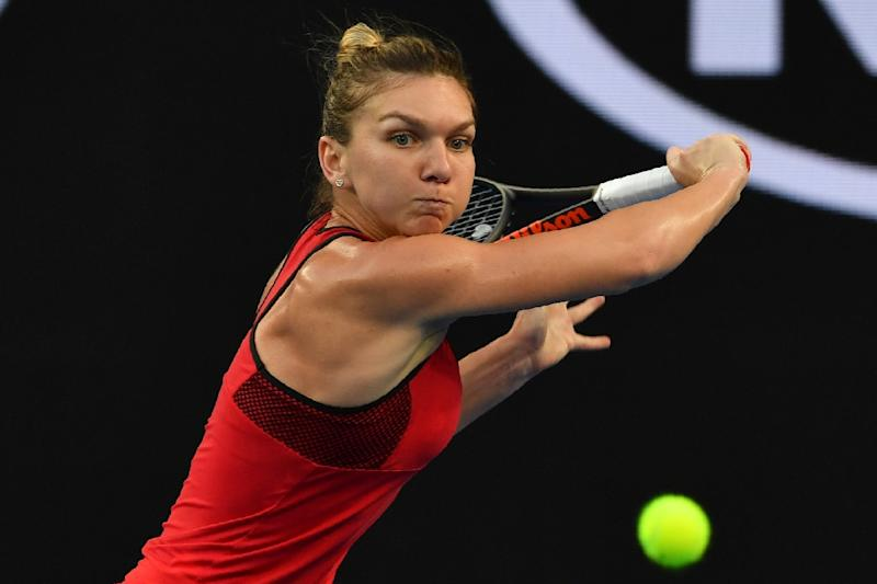 Romania's Simona Halep hits a return to Canada's Eugenie Bouchard during their second round singles match on day four of the Australian Open in Melbourne on January 18, 2018