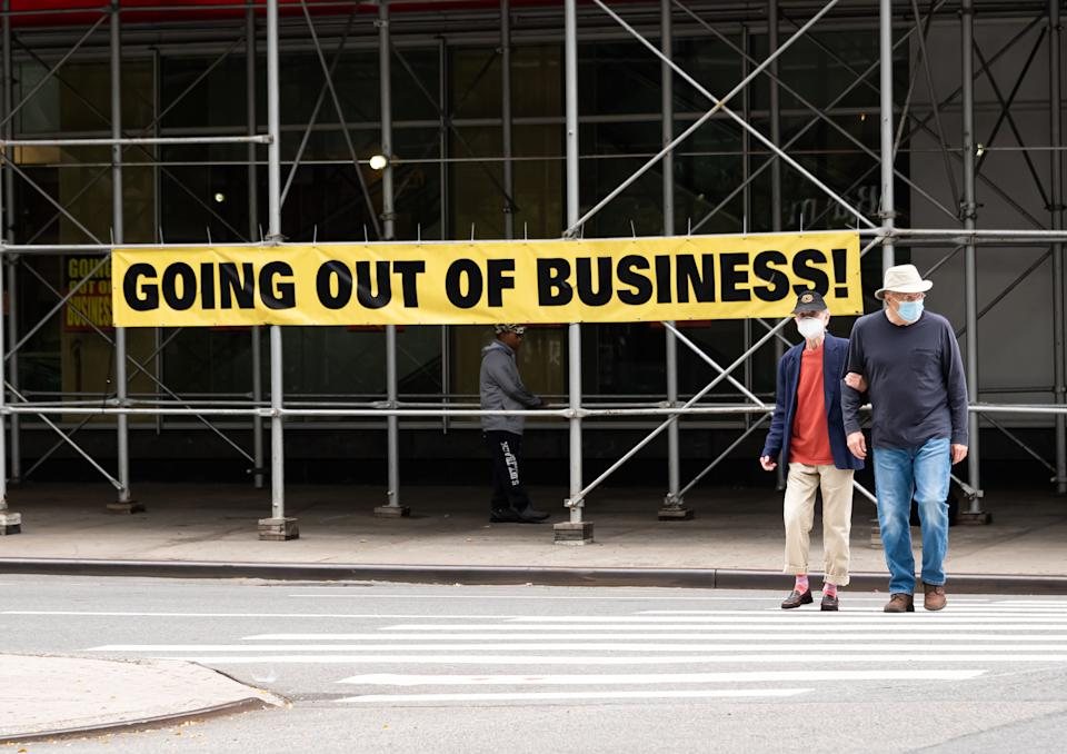 NEW YORK, NEW YORK - SEPTEMBER 27: People wearing protective masks walk by a going out of business sign displayed outside Century 21 on the Upper West Side as the city continues Phase 4 of re-opening following restrictions imposed to slow the spread of coronavirus on September 27, 2020 in New York City. The fourth phase allows outdoor arts and entertainment, sporting events without fans and media production. (Photo by Noam Galai/Getty Images)