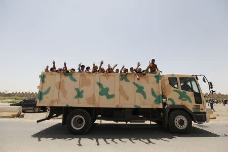 Volunteers who have joined the Iraqi army to fight against the predominantly Sunni militants, who have taken over Mosul and other Northern provinces, travel in an army truck, in Baghdad, June 12, 2014. REUTERS/Ahmed Saad