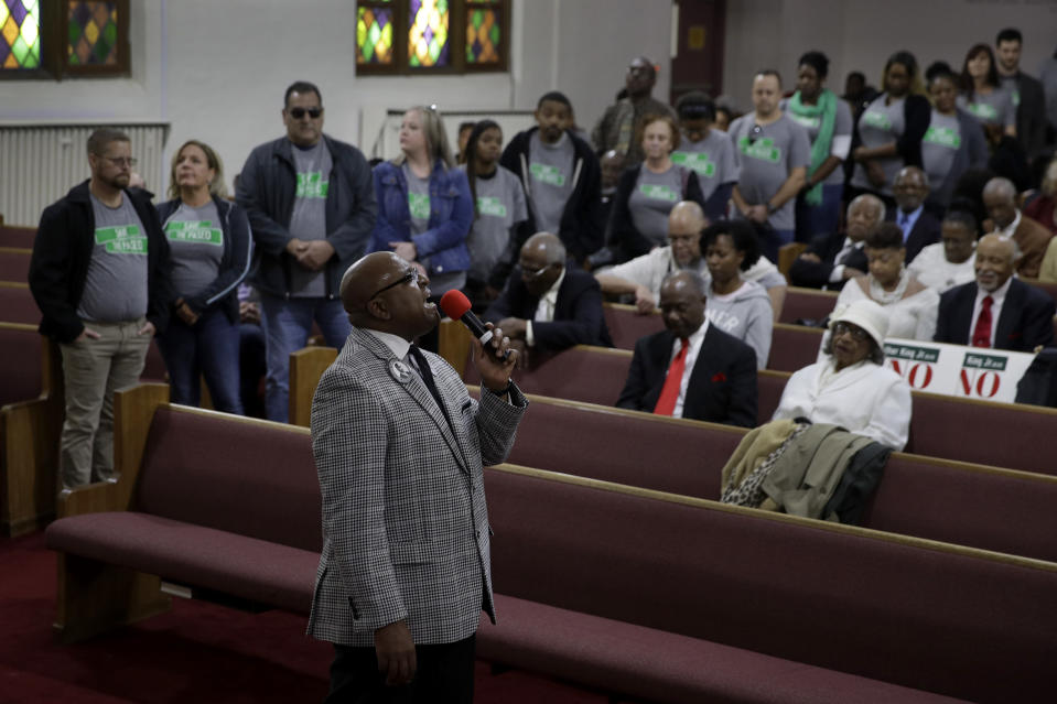 "In this Sunday, Nov. 3, 2019, photo, people wearing ""Save The Paseo"" shirts stand among attendees at a rally to keep a street named in honor of Dr. Martin Luther King Jr. while Rev. Vernon Howard speaks at Paseo Baptist Church in Kansas City, Mo. In January, the City Council voted to rename one of the city's main boulevards, The Paseo, after King, but many in the community want the old name back. A petition drive put the issue on the Nov. 5 ballot pitting neighbors against each other. Ministers who pushed for the change worry about the message that will be sent if King's name is removed. (AP Photo/Charlie Riedel)"