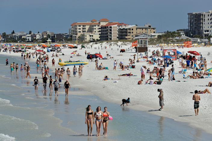 Visitors enjoy Clearwater Beach, Wednesday, March 18, 2020, in Clearwater Beach, Fla. Beach goers are keeping a safe distance from each other to help protect from the spread of the  new coronavirus.