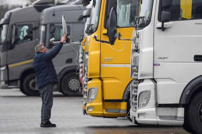 A Hungarian truck driver adjusts a satellite dish for viewing television on the front of his lorry whilst he waits at Ashford International Truck Stop, in Ashford