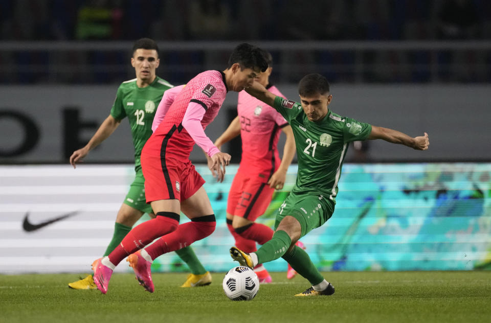 South Korea's Son Heung-min, left, fights for the ball against Turkmenistan's Halmammedov Rovshengeldi during their Asian zone Group H qualifying soccer match for the FIFA World Cup Qatar 2022 at Goyang stadium in Goyang, South Korea, Saturday, June 5, 2021. (AP Photo/Lee Jin-man)
