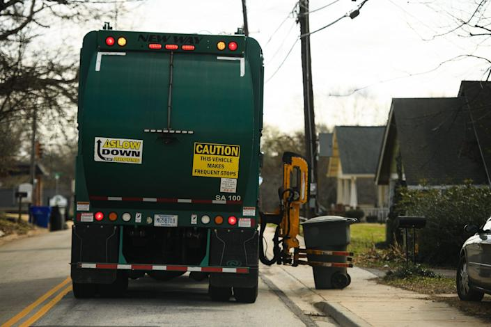 A garbage truck collects trash from a residence Wednesday, Jan. 27, 2021.
