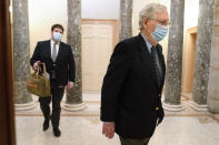 Followed by a staffer holding a bag, Senate Majority Leader Mitch McConnell of Ky., right, leaves the Capitol for the day, Tuesday, Dec. 29, 2020, on Capitol Hill in Washington. (AP Photo/Jacquelyn Martin)