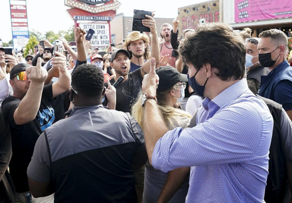 Justin Trudeau gives a thumbs up to protesters giving him the middle finger and shouting at him.