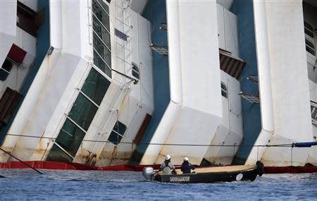Salvage crew workers follow an operation to raise the capsized cruise liner Costa Concordia from a boat next to it, outside Giglio harbour September 16, 2013. REUTERS/Tony Gentile