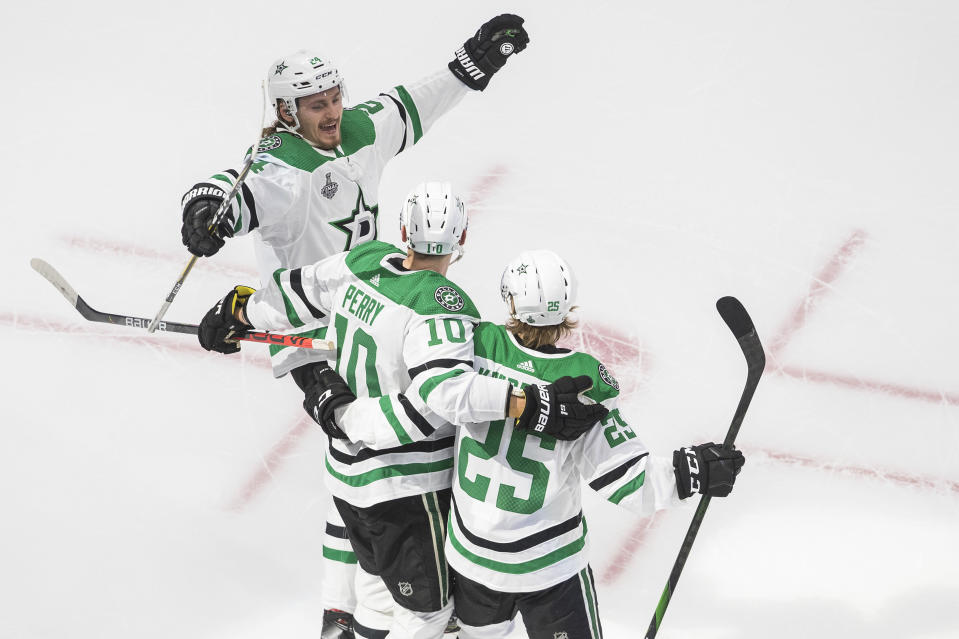Dallas Stars' Joel Kiviranta (25) celebrates his goal with teammates right wing Corey Perry (10) and Dallas Stars left wing Roope Hintz (24) against the Tampa Bay Lightning during second-period NHL Stanley Cup finals hockey action in Edmonton, Alberta, Saturday, Sept. 19, 2020. (Jason Franson/The Canadian Press via AP)