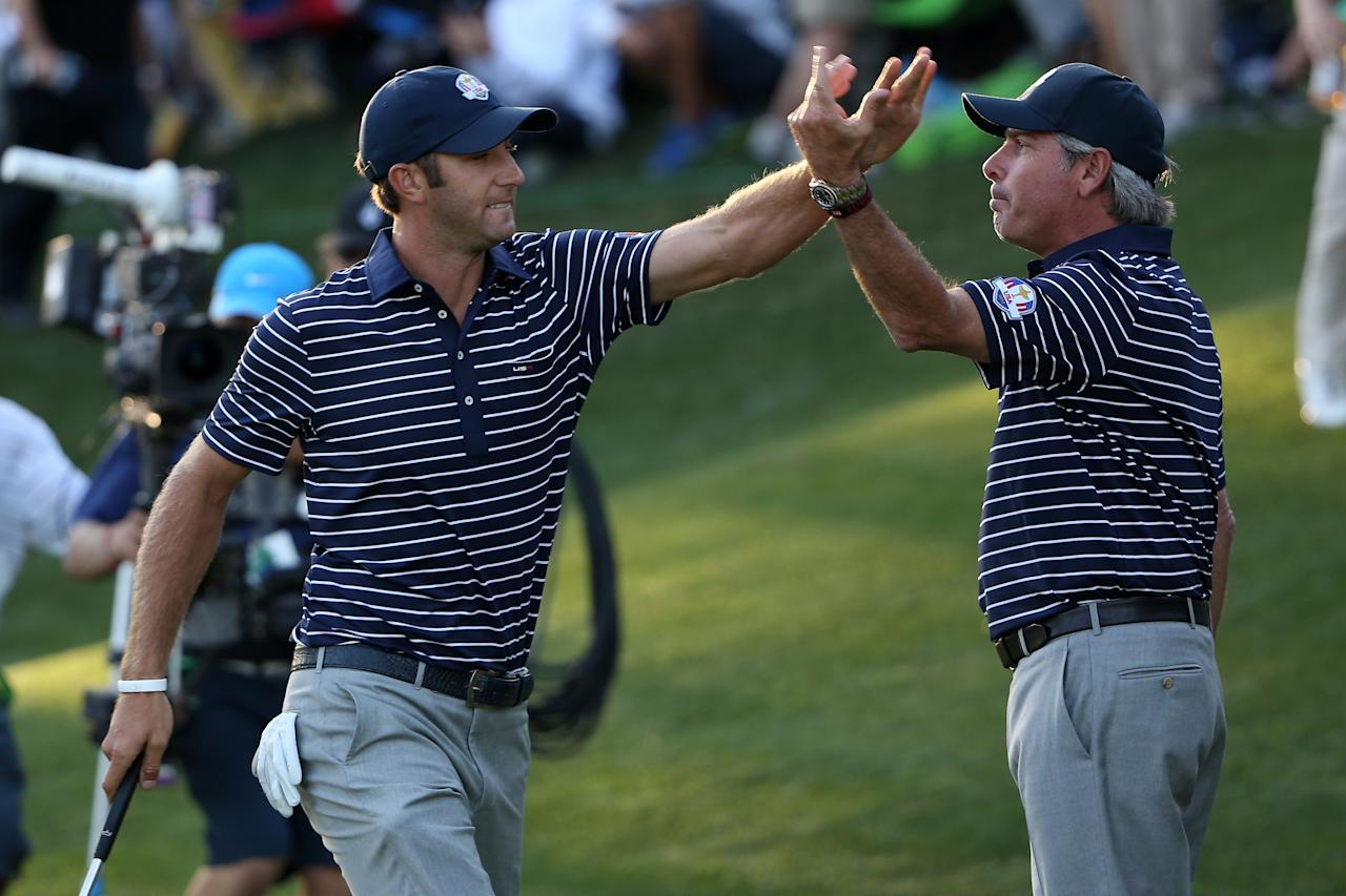 MEDINAH, IL - SEPTEMBER 29:  Dustin Johnson of the USA (L) celebrates his birdie putt on the 17th green with Fred Couples during day two of the Afternoon Four-Ball Matches for The 39th Ryder Cup at Medinah Country Club on September 29, 2012 in Medinah, Illinois.  (Photo by Ross Kinnaird/Getty Images)