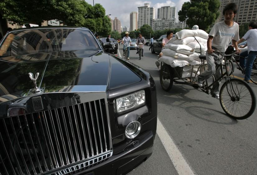 SHANGHAI, CHINA - SEPTEMBER 25: (CHINA OUT) A passer-by rides a tricycle past a Rolls-Royce Phantom parked outside a new Rolls-Royce showroom during its opening ceremony on September 25, 2007 in Shanghai, China. China has now overtaken Japan to become the largest market for the luxury British Rolls-Royce brand in Asia, and the third in the world. In 2006 over 40 of the luxury sedan were sold in Chinese mainland. (Photo by China Photos/Getty Images)