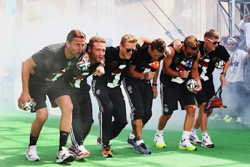 """German soccer players from left: Roman Weidenfeller, Shkodran Mustafi, Andre Schuerrle, Miroslav Klose, Mario Goetze and Toni Kroos celebrate on stage at the German team victory ceremony , near the Brandenburg Gate in Berlin, Tuesday July 15, 2014. Germany's World Cup winners shared their fourth title with hundreds of thousands of fans by parading the trophy through cheering throngs to celebrate at the Brandenburg Gate on Tuesday. An estimated 400,000 people packed the """"fan mile"""" in front of the Berlin landmark to welcome home coach Joachim Loew's team and the trophy which returned to Germany for the first time in 24 years. (AP Photo/ Alex Grimm,Pool)"""