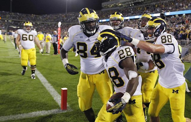 Michigan running back Fitzgerald Toussaint (28) is congratulated by teammates after his fourth-quarter touchdown against Connecticut in an NCAA college football game, Saturday, Sept. 21, 2013, in East Hartford, Conn. Michigan won 24-21. (AP Photo/Charles Krupa)