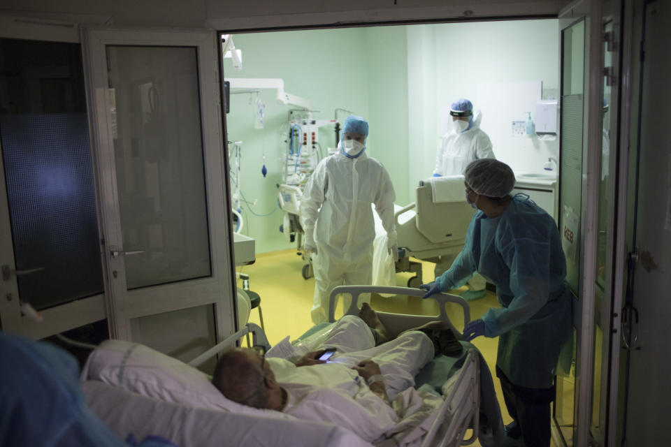 A medical crew receive a COVID-19 patient into the intensive care unit at the Joseph Imbert Hospital Center in Arles, southern France, Wednesday, Oct. 28, 2020. Many French doctors are urging a new nationwide lockdown, noting that 58% of the country's intensive care units are now occupied by COVID patients and medical staff are under increasing strain. (AP Photo/Daniel Cole)