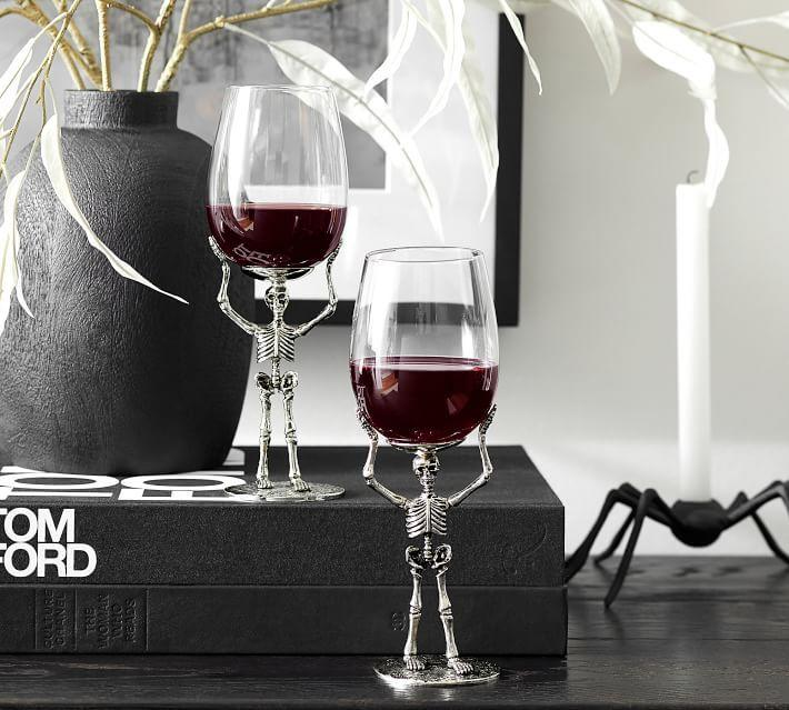 """<p><strong></strong></p><p>potterybarn.com</p><p><strong>$23.50</strong></p><p><a href=""""https://go.redirectingat.com?id=74968X1596630&url=https%3A%2F%2Fwww.potterybarn.com%2Fproducts%2Fskeleton-wine-glass&sref=https%3A%2F%2Fwww.housebeautiful.com%2Fshopping%2Fhome-accessories%2Fg33535237%2Fpottery-barn-halloween-decor-collection-2020%2F"""" target=""""_blank"""">BUY NOW</a></p><p>Skeleton hands add a delightfully creepy touch to these wine glasses, which are currently on sale. You can also enjoy witch's brew and other <a href=""""https://www.housebeautiful.com/lifestyle/recipes-cookbooks/g3669/halloween-cocktails/"""" target=""""_blank"""">Halloween cocktails</a>, from <a href=""""https://www.potterybarn.com/products/skeleton-hand-flute/"""" target=""""_blank"""">skeleton hand glassware</a> and even a<a href=""""https://www.potterybarn.com/products/skeleton-hand-serving-punch-bowl/"""" target=""""_blank""""> large skeleton hand punch bowl</a>.</p>"""