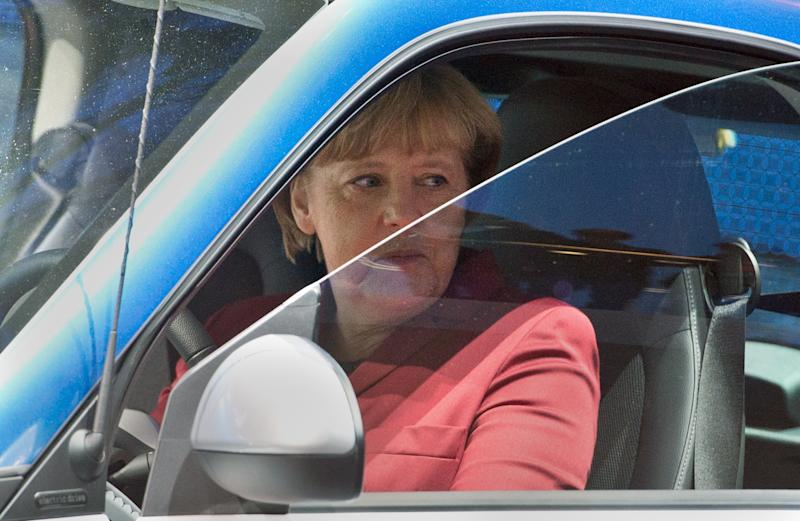 German Chancellor Angela Merkel tests a Smart Electric Drive at the International Motor Show (IAA) in Frankfurt, on September 12, 2013 (AFP Photo/Boris Roessler)