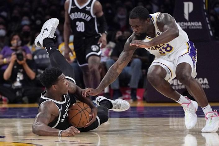 Brooklyn Nets forward Devontae Cacok, left, goes after a loose ball.