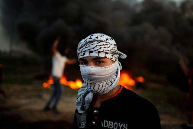 """<p>A Palestinian protester, who identified himself as Ahmed, poses for a photograph in front of burning tires at the scene of clashes with Israeli troops near the border with Israel, east of Gaza City, Jan. 12, 2018. """"We are the fuel of the Intifada, but we are hungry and at home we have no electricity and our fathers have no jobs. This can't bring about anything except an explosion,"""" he said. (Photo: Mohammed Salem/Reuters) </p>"""