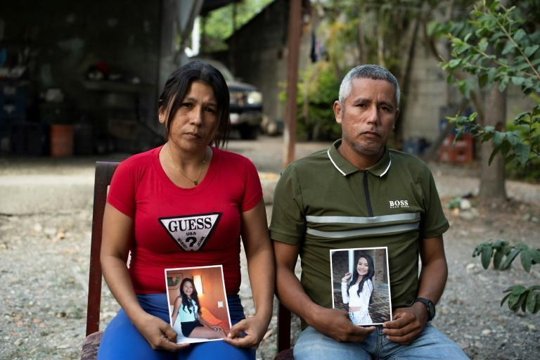Mileidys Torrealba (L) and Eduard Jose Falcon display pictures of their murdered daughter Eduarlis Falcon