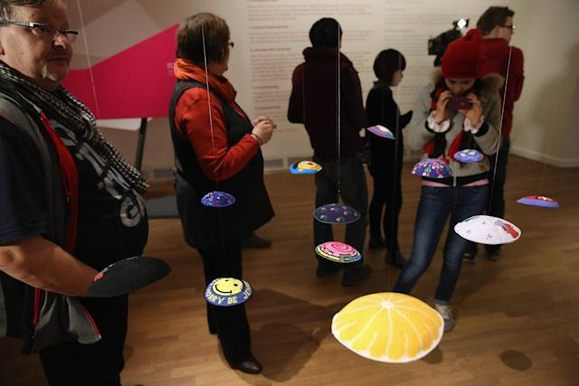 "BERLIN, GERMANY - APRIL 04: Visitors walk through an exhibit that features yarmulkas, hats and other headwear at the exhibition ""The Whole Truth - Everything You Always Wanted To Know About Jews . . . "" at the Juedisches Museum (Jewish Museum) on April 4, 2013 in Berlin, Germany. The exhibition presents every-day aspects of Jewish life, poses simple questions answered with exhibits and challenges certain stereotypes. However its live exhibit, which features a Jewish person who sits in a plastic enclosure open on one side for several hours a day to answer visitors' questions, has sparked criticism from some Jewish groups. (Photo by Sean Gallup/Getty Images)"