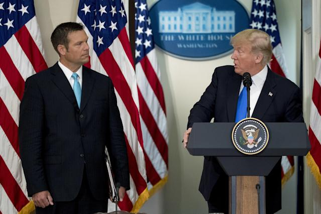 President Donald Trump speaks as Kris Kobach, Kansass secretary of state, listens during the initial meeting of the Presidential Advisory Commission on Election Integrity in Washington, D.C., July 19, 2017. (Andrew Harrer/Bloomberg via Getty Images)