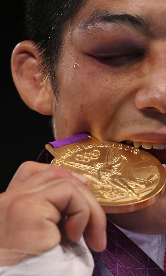 South Korea's Hyeonwoo Kim bites his gold medal at the podium of Men's 66Kg Greco-Roman wrestling at the ExCel venue during the London 2012 Olympic Games August 7, 2012.                     REUTERS/Damir Sagolj (BRITAIN  - Tags: OLYMPICS SPORT WRESTLING)