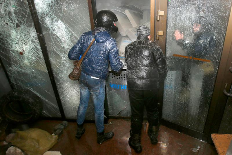 Protesters negotiate with police during an attack of the Ukrainian House building in central Kiev, Ukraine, early Sunday, Jan. 26, 2014. New violence erupted in Ukraine's capital during the night as a large crowd attacked the government exposition and conference hall where police were stationed inside. Early Sunday, demonstrators were throwing firebombs into the Ukrainian House building and setting off fireworks, and police responded with tear gas. (AP Photo/Sergei Grits)