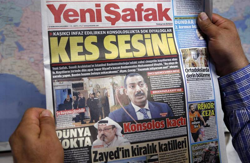 A man holds Yeni Safak newspaper with a headline that reads